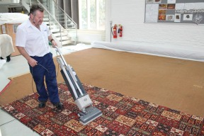 Vacuuming sacrificial carpet with historic carpet face down below